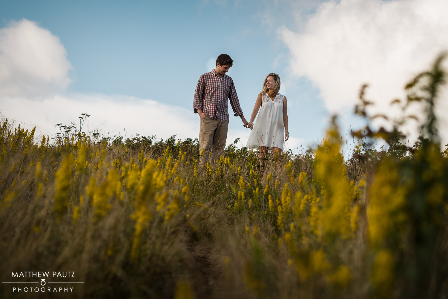 engaged couple walking in field of wildflowers